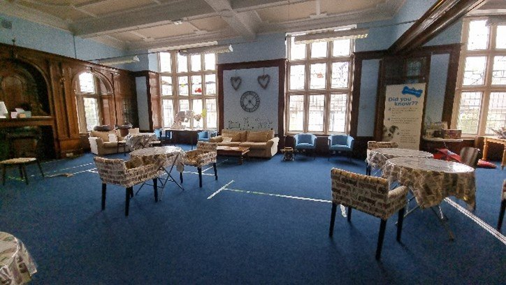 Room with tables and chairs for visitors to sit at and have a drink and a biscuit
