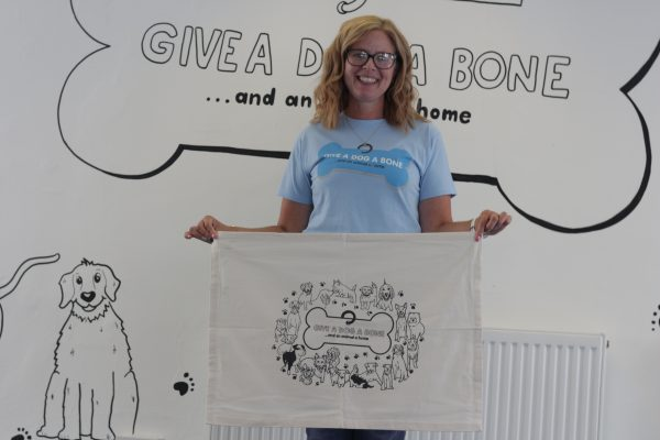 White tea towel with logo design featuring illustrations of the dogs of some of our supporters..