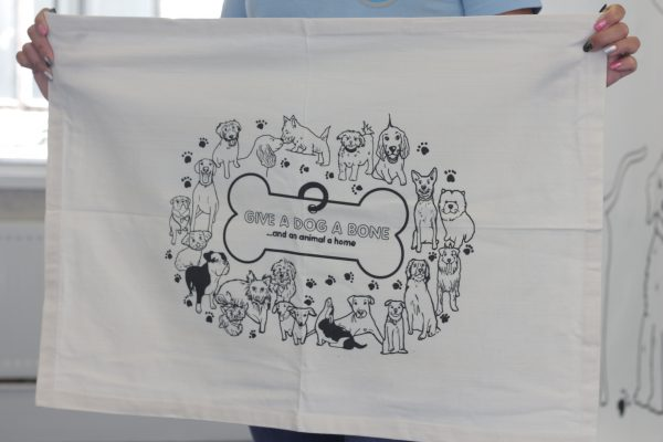 Close up of white tea towel with logo design featuring the dogs of some of our supporters.